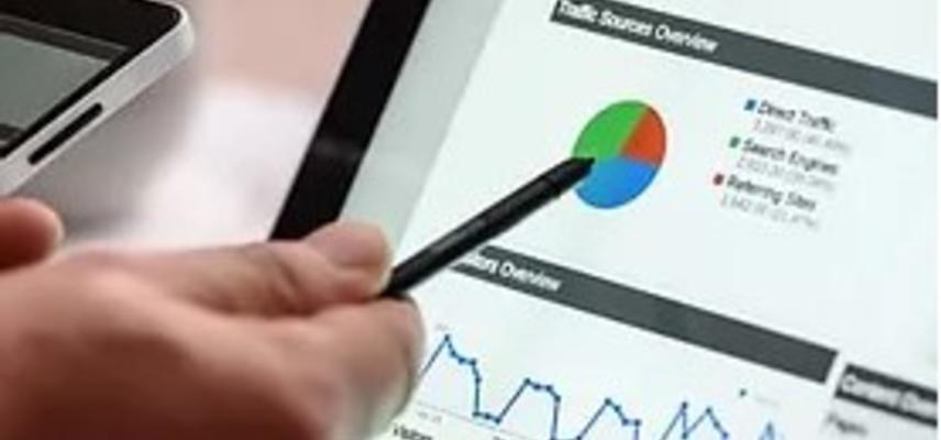 A hand holds a pen against a computer screen with analytics data.
