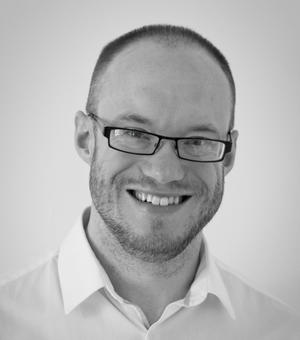 Black and white photograph of Dr Andrew Cusworth, smiling, and wearing a white shirt.